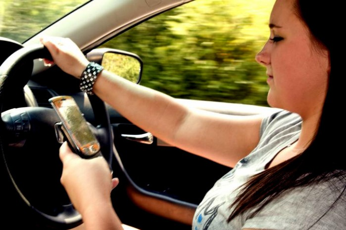 Woman looking at cell phone while driving.